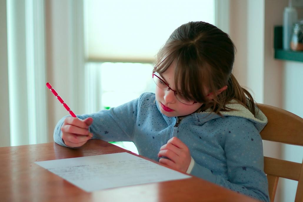 Bambina compila tabella compiti per progetto ascolto estensivo