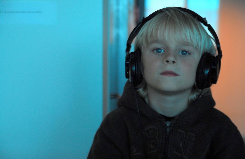Bambino ascolta tracce di ascolto estensivo in cuffia