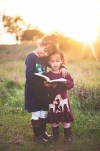 due_bambine_leggono_letture_in_inglese_in_giardino