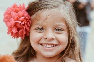 bambina_sorride_fiore_capelli